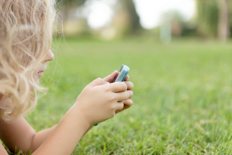 Muchacha con los móviles que se reclinan sobre la hierba imágenes de archivo libres de regalías