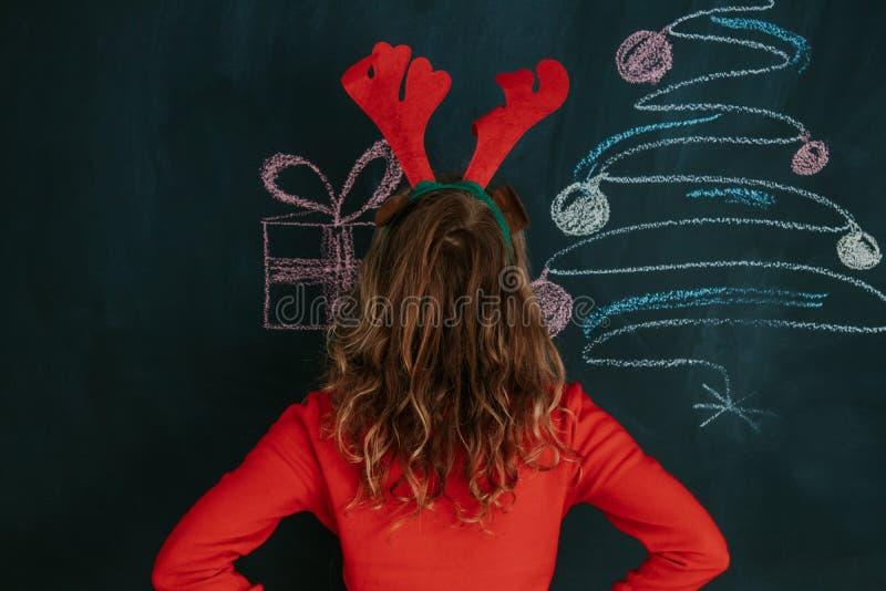 Muchacha con los oídos y la Navidad del reno fotos de archivo