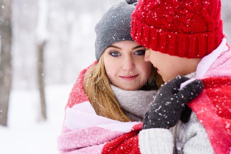 Muchacha con los ojos azules en abrazos de su novio que mira la cámara imagenes de archivo