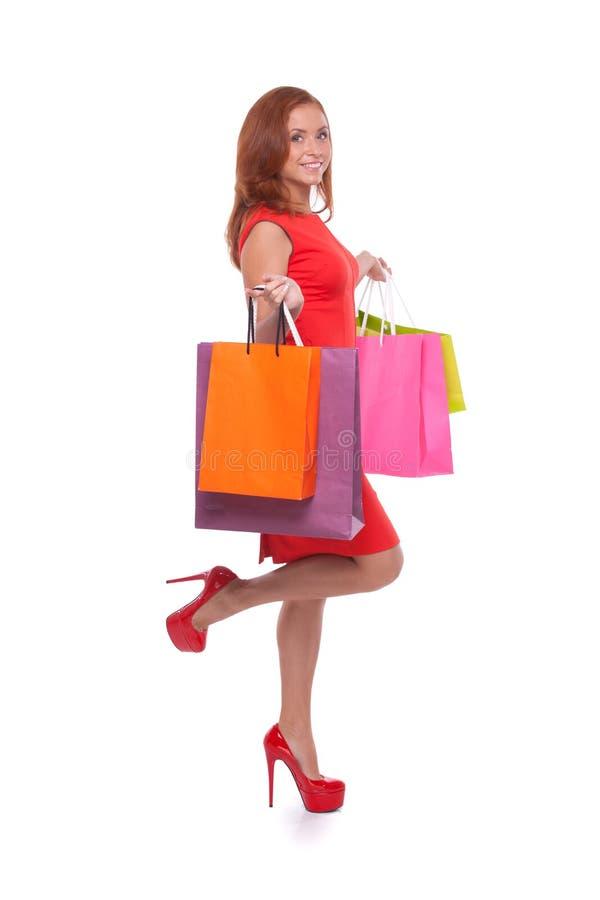 Muchacha con los panieres. Vista lateral integral de la mujer joven alegre en el vestido rojo que sostiene los panieres y que sonr foto de archivo libre de regalías