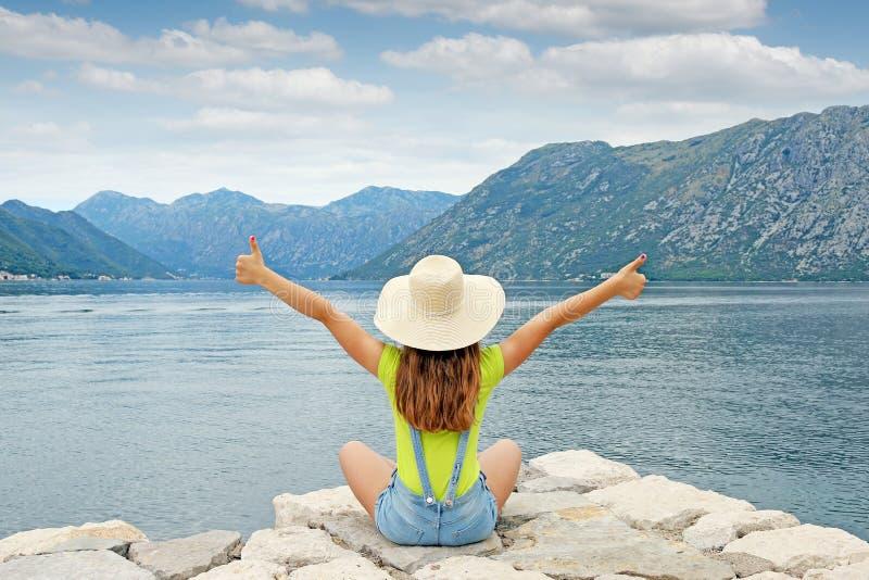 Muchacha con los pulgares para arriba en la bahía de Kotor de las vacaciones de verano imágenes de archivo libres de regalías
