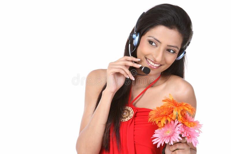Muchacha con los teléfonos y las flores micro de la margarita imagenes de archivo