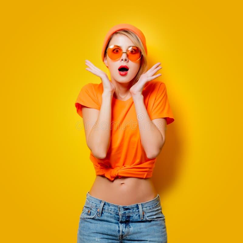Muchacha con los vidrios anaranjados en fondo amarillo fotos de archivo