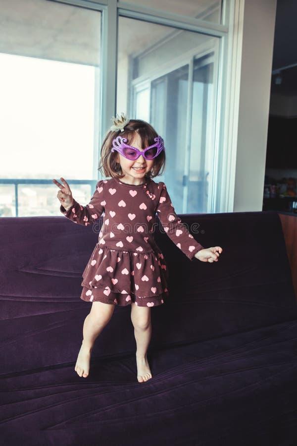 muchacha con los vidrios divertidos que saltan el baile en el sofá dentro foto de archivo libre de regalías