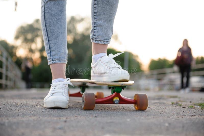 Muchacha con los zapatos de las zapatillas de deporte del longboard que llevan en estilo urbano fotos de archivo
