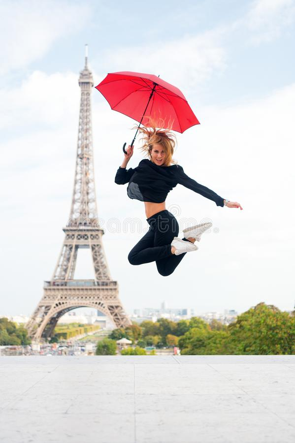 Muchacha con mirada de la belleza en la torre Eiffel La mujer salta con el paraguas de la moda Parisiense aislado en el fondo bla fotografía de archivo libre de regalías