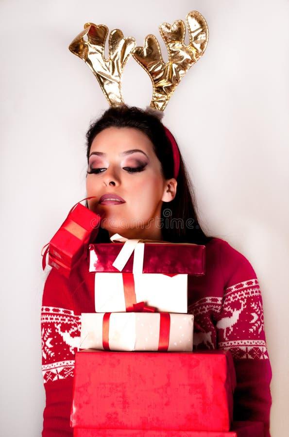 Muchacha con muchas cajas de regalo y una caída de la caja Cuernos del reno en el suéter principal y rojo imágenes de archivo libres de regalías