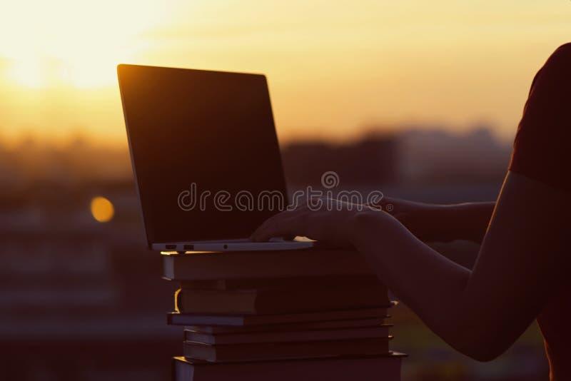 Muchacha con muchos libros y ordenador portátil en fondo de la puesta del sol Preparación para los exámenes de la universidad Con imagen de archivo