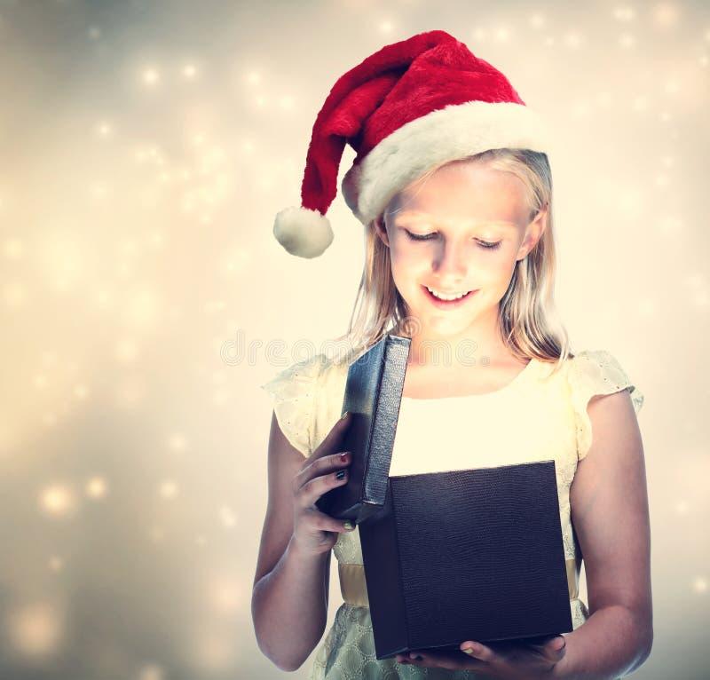 Muchacha con Santa Hat Opening Gift Box imagen de archivo libre de regalías