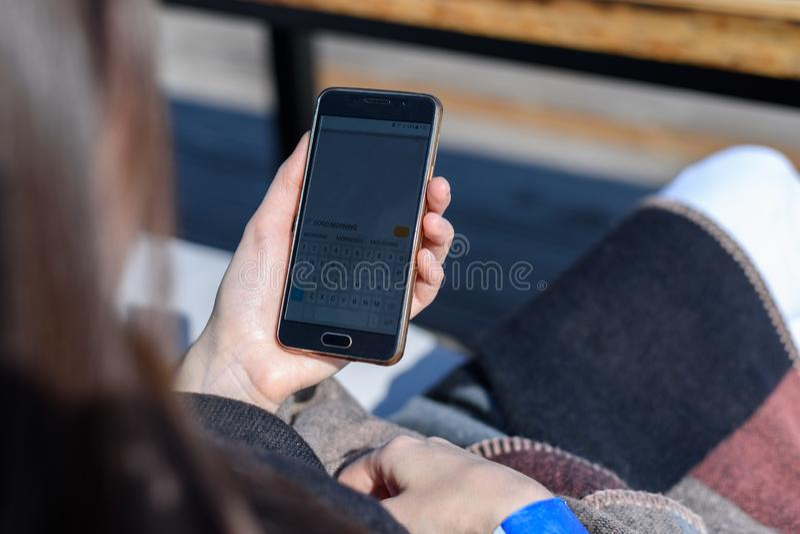 Muchacha con smartphone a disposición de la parte posterior en la terraza de un café del verano, buena mañana del mensaje imágenes de archivo libres de regalías