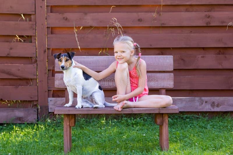 Muchacha con su perro que se sienta en banco de madera imagenes de archivo