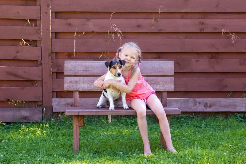 Muchacha con su perro que se sienta en banco de madera imagen de archivo libre de regalías