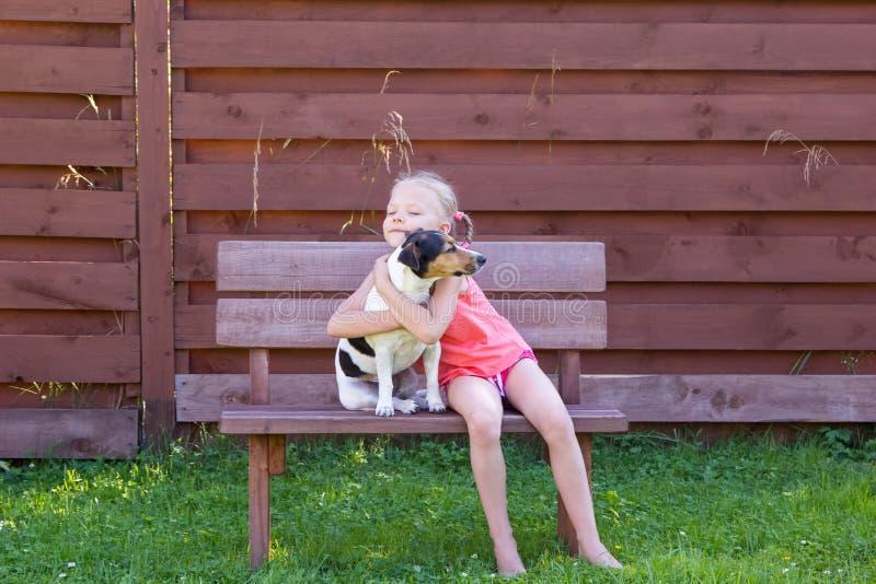 Muchacha con su perro que se sienta en banco de madera imágenes de archivo libres de regalías