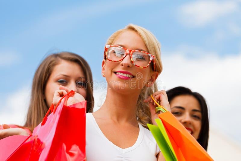 Muchacha con sus amigos después de hacer compras fotos de archivo libres de regalías