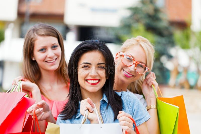 Muchacha con sus amigos después de hacer compras foto de archivo
