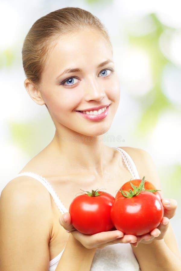 Muchacha con tres tomates rojos foto de archivo