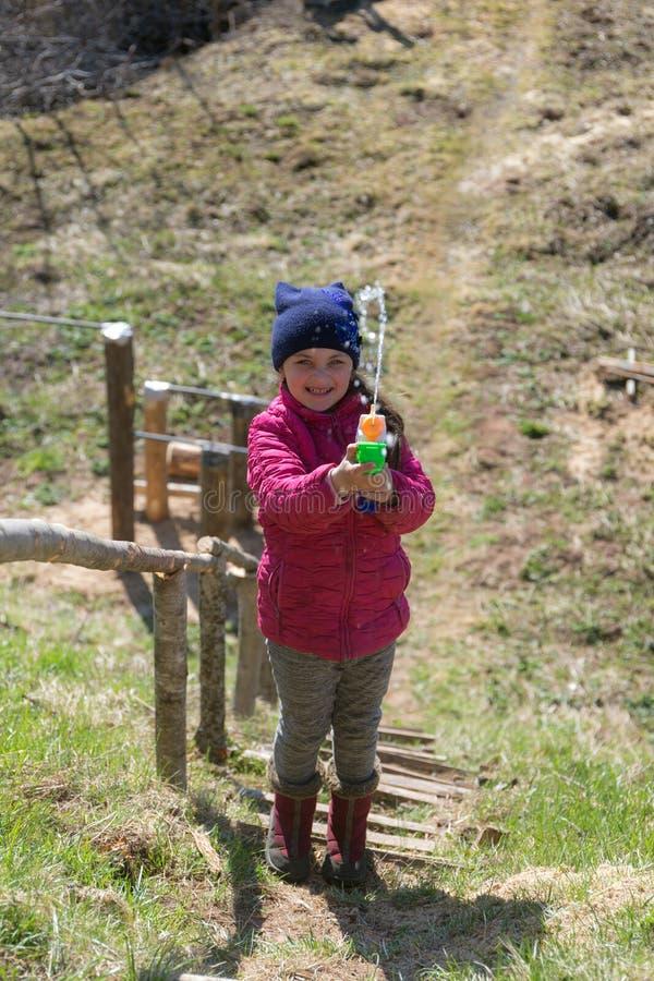 Muchacha con un arma de agua del juguete foto de archivo