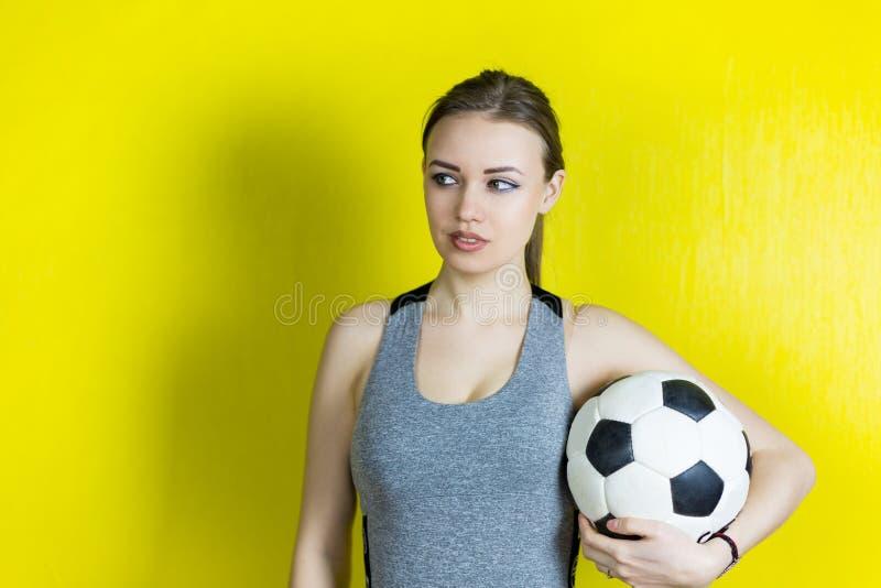 Muchacha con un balón de fútbol en un fondo amarillo imágenes de archivo libres de regalías