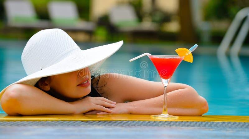 Muchacha con un cóctel en el borde de la piscina fotografía de archivo