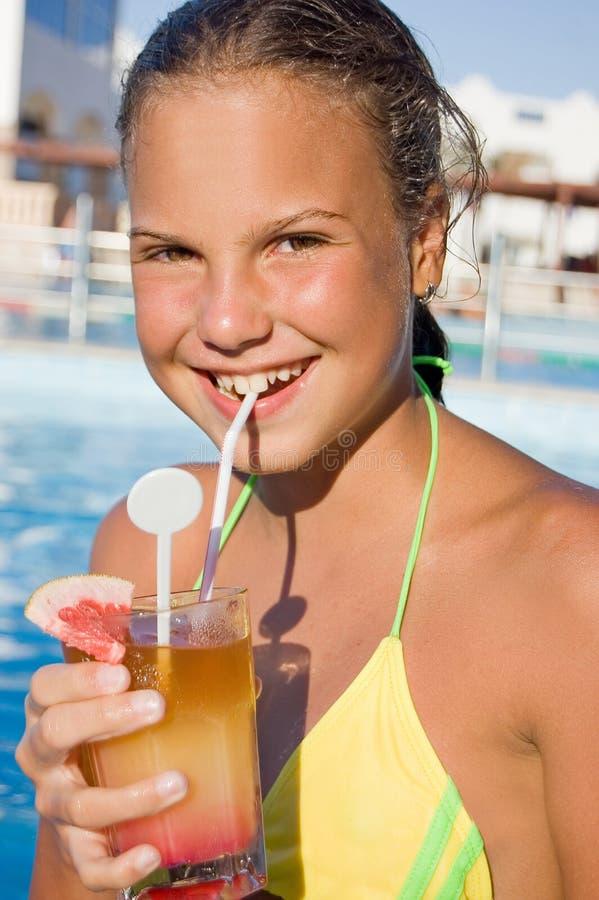 Muchacha con un coctel en la piscina fotos de archivo