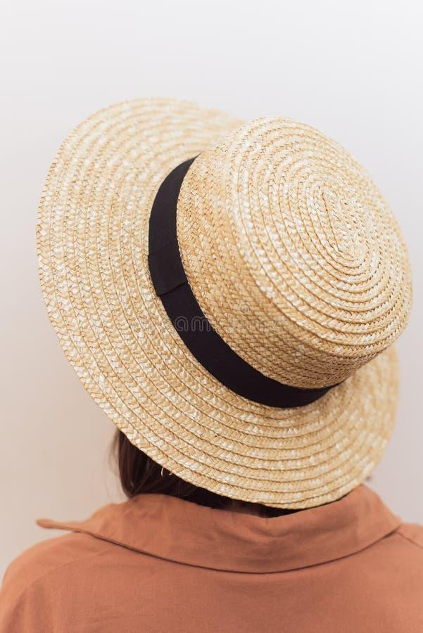 Muchacha con un cuadrado en un sombrero de paja en un fondo blanco fotografía de archivo