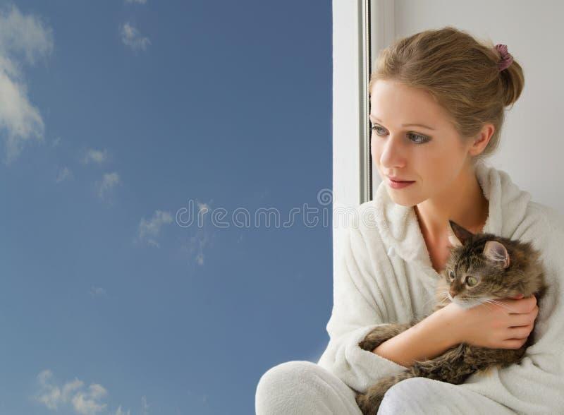 muchacha con un gato que mira hacia fuera la ventana foto de archivo