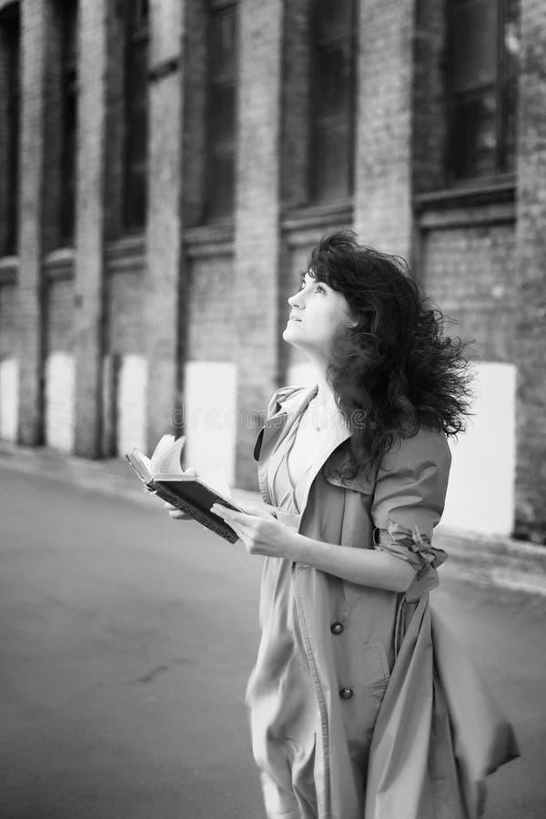 Muchacha con un libro en el fondo del edificio industrial fotografía de archivo libre de regalías