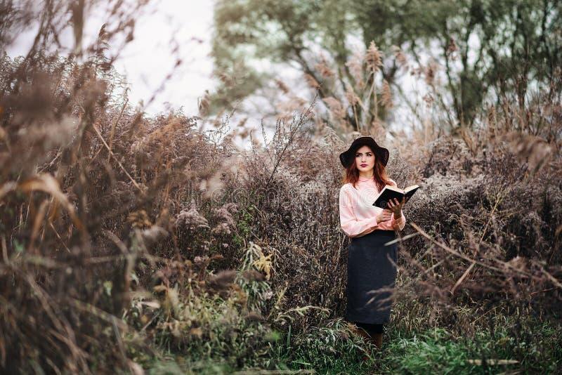 Muchacha con un libro en las manos de soportes overgrown en el centro fotografía de archivo
