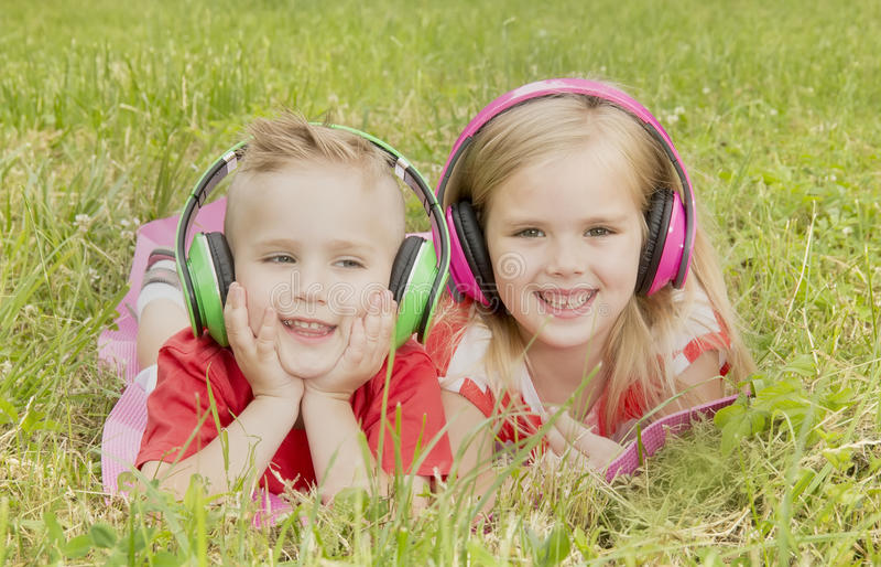 Muchacha con un muchacho en auriculares que escucha la música imagen de archivo libre de regalías