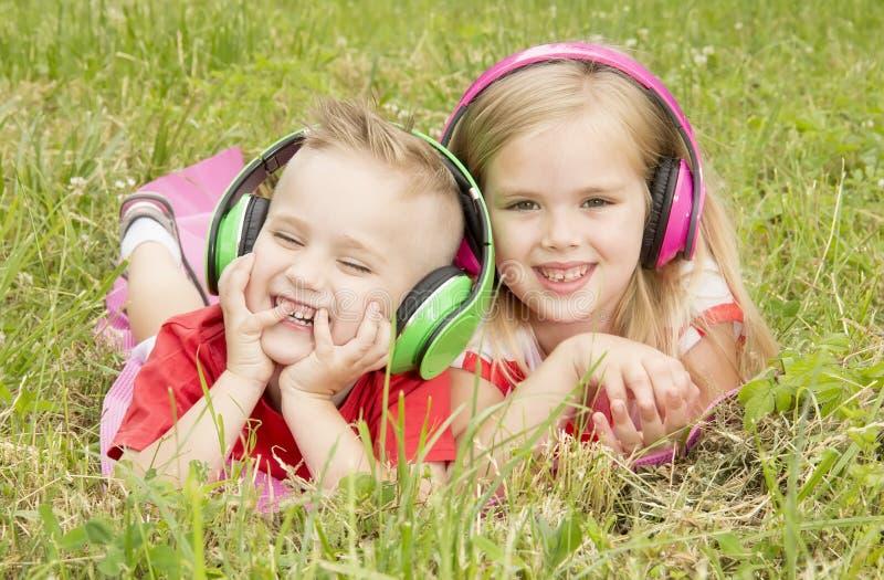 Muchacha con un muchacho en auriculares que escucha la música imagen de archivo