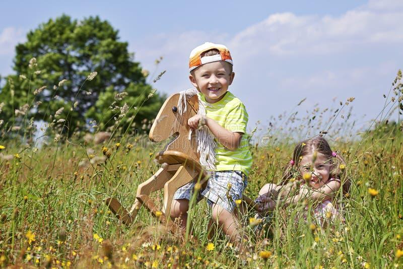 Muchacha con un muchacho que monta un caballo imagenes de archivo
