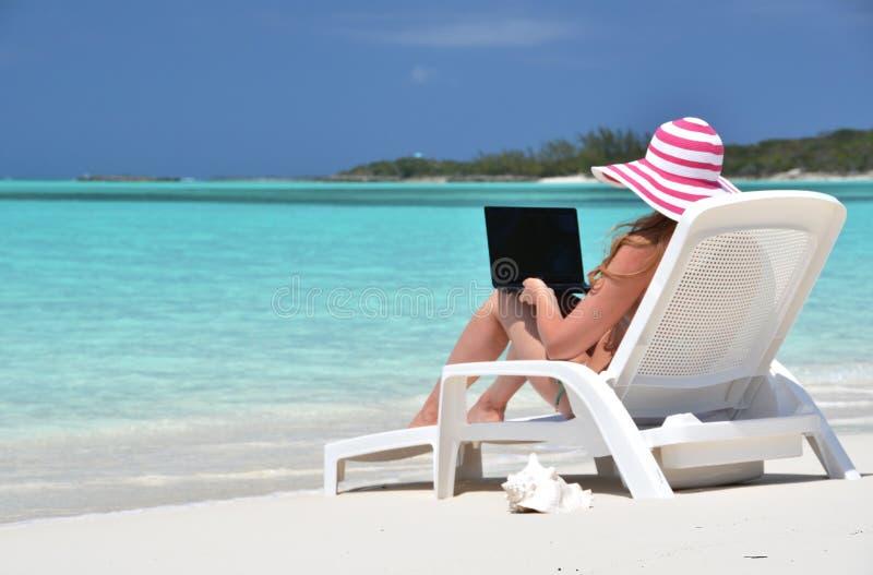 Muchacha con un ordenador portátil en la playa tropical fotos de archivo