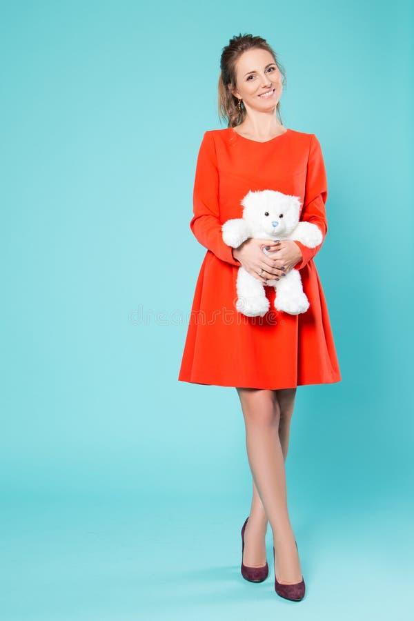 Muchacha con un oso de peluche en un vestido rojo en un fondo azul fotografía de archivo