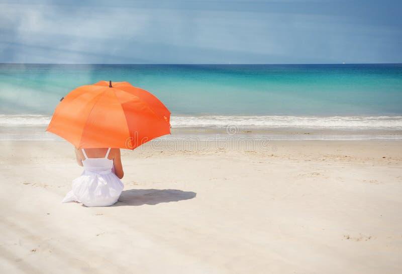 Muchacha con un paraguas anaranjado foto de archivo libre de regalías
