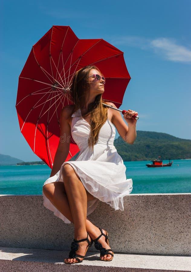 Muchacha con un paraguas contra el mar imagenes de archivo