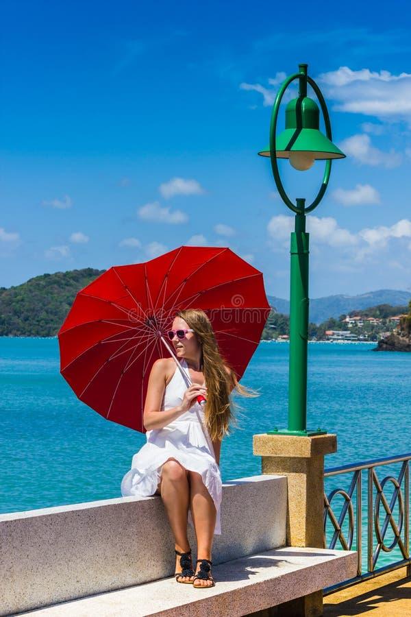 Muchacha con un paraguas contra el mar foto de archivo