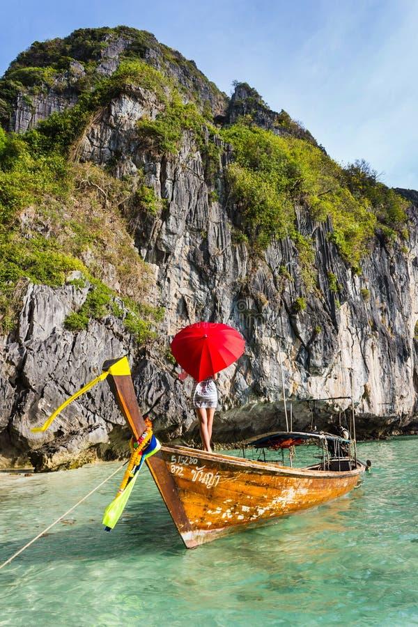 Muchacha con un paraguas rojo en un barco en un centro turístico fotos de archivo