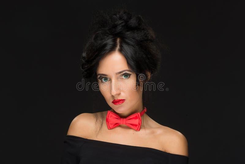 Muchacha con un peinado complicado en un negro imagen de archivo