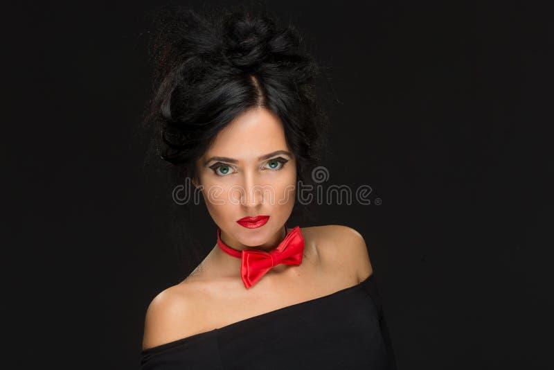Muchacha con un peinado complicado en un negro foto de archivo