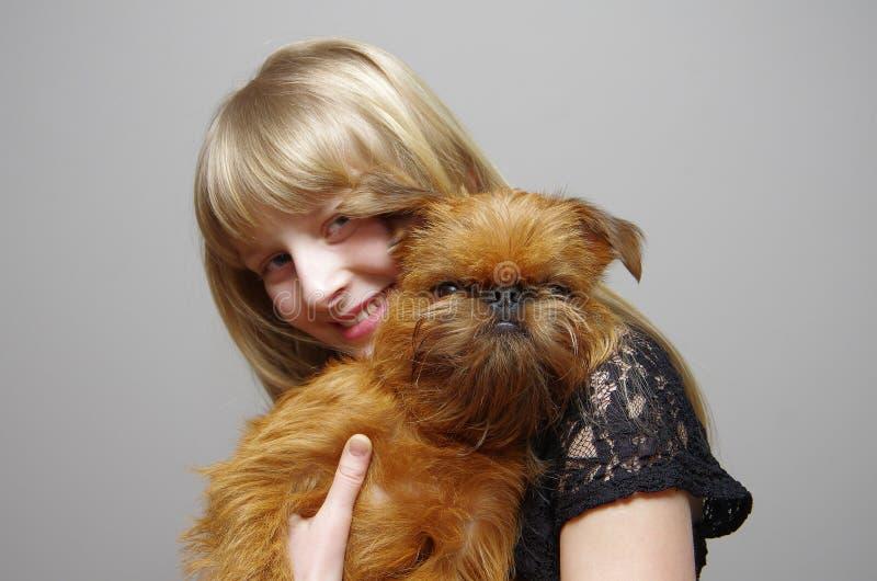 Muchacha con un perro Bruselas Griffon fotografía de archivo libre de regalías