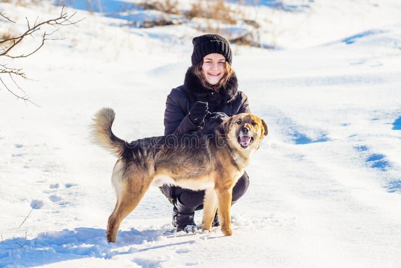 Muchacha con un perro en el invierno en un paseo Muchacha y perro contra la perspectiva del snow_ blanco imagen de archivo libre de regalías