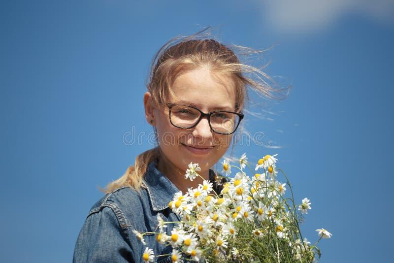 Muchacha con un ramo de margaritas en un fondo del cielo azul foto de archivo