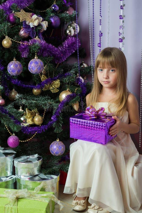 Muchacha con un regalo que se sienta debajo del árbol de navidad imagenes de archivo