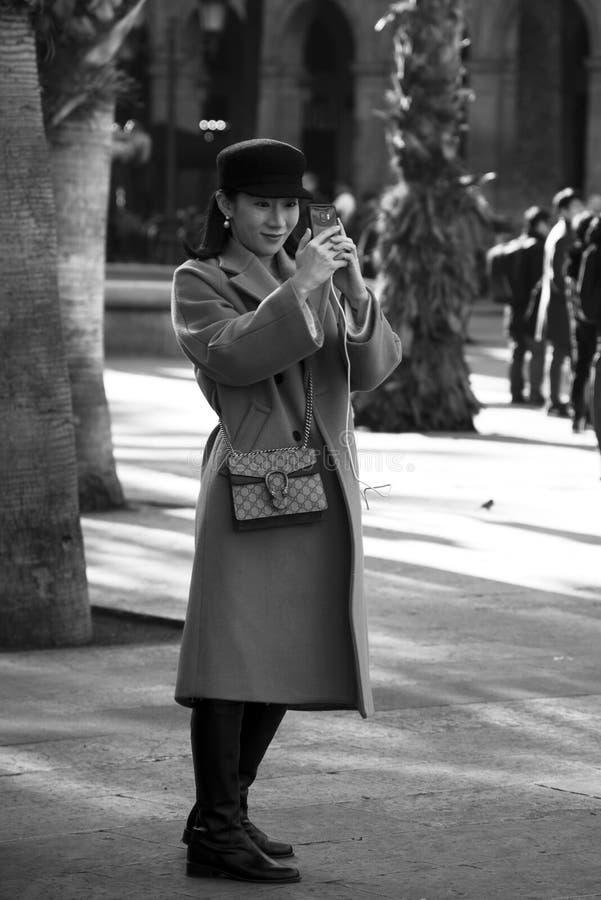 Muchacha con un smartphone en la plaza real de Barcelona, Cataluña, España imagen de archivo libre de regalías