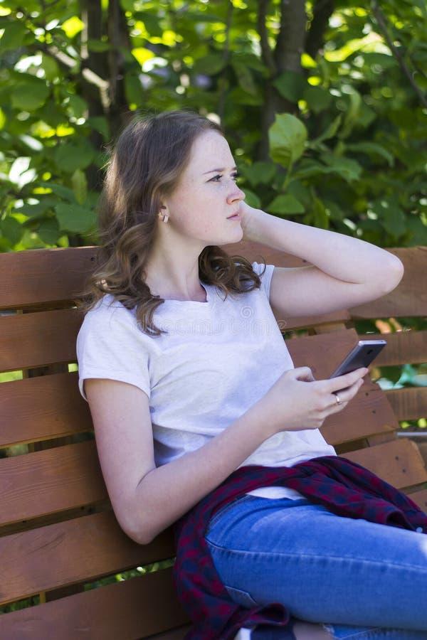 Muchacha con un teléfono en un banco imágenes de archivo libres de regalías