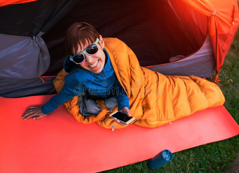 Muchacha con un teléfono en un saco de dormir imagen de archivo