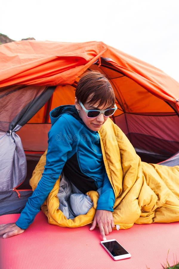 Muchacha con un teléfono en un saco de dormir imagen de archivo libre de regalías