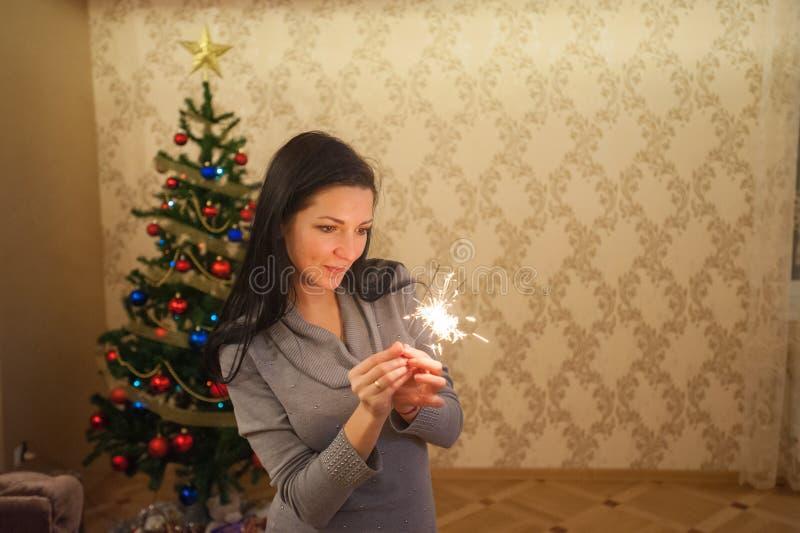 Muchacha con una bengala cerca del árbol de navidad Una mujer joven alegre con una sonrisa linda en un suéter hecho punto se está foto de archivo libre de regalías