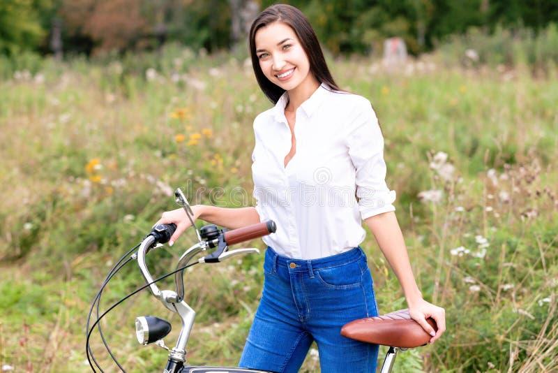 Muchacha con una bicicleta que presenta al aire libre fotografía de archivo libre de regalías