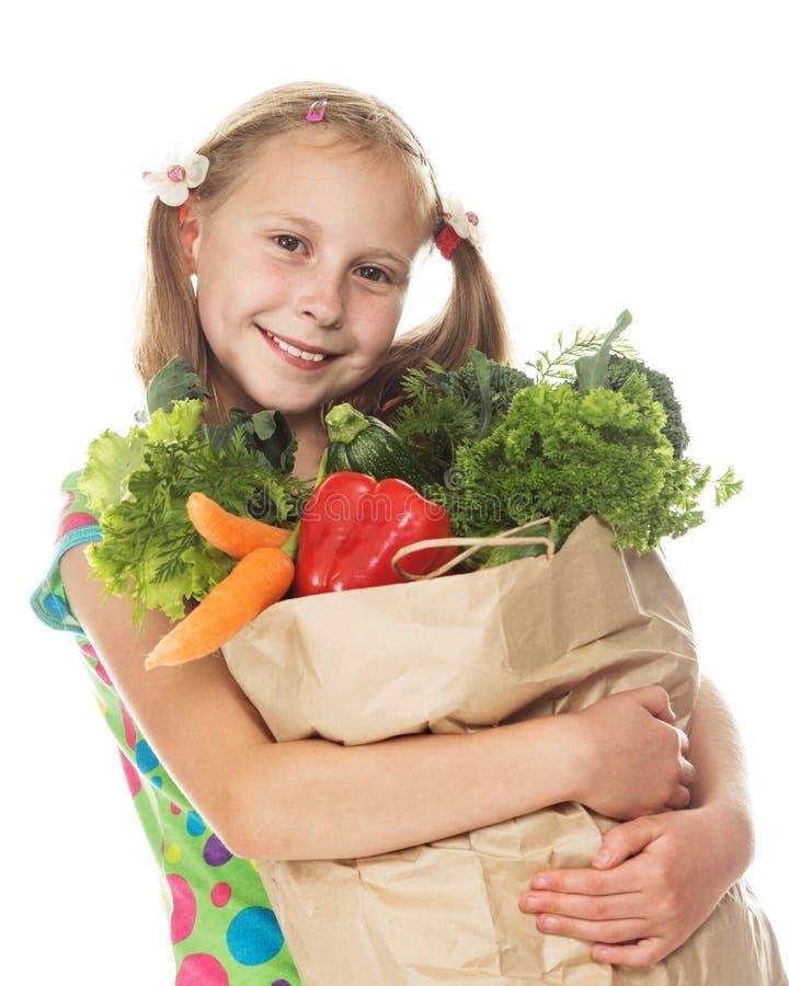 Muchacha con una bolsa de papel con las verduras fotografía de archivo